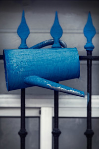 Bue watering can hanging on a fense