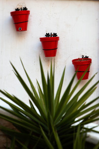 Three red flower pots hanging on white wall