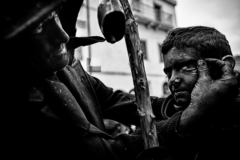 March 2014 - Lula, Sardinia – Italy.  Father blackens his son's face with cork ash. Every year during carnival, the archaic rite of Dionysus' death is enacted in the streets of this little village.