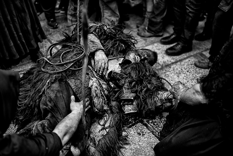 """February 2016- Lula, Sardinia – Italy. """"Su Battileddu"""", """"the crazy"""", the sacrificial victim. The term """"battile"""" indicates in fact a useless and incompetent person. The archaic rite of the Lula carnival expected, in the distant past, the sacrifice of a victim in the flesh and bones. Today su Battileddu wears sheepskins, his face is painted in black and the lips in red and carries some big cowbells on his shoulders."""