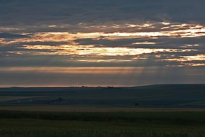 In the distance, rain streaks across the low hills/