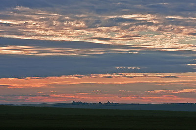As the sun penetrates the clouds, a pastel sunrise spreads across the prairie horizon.