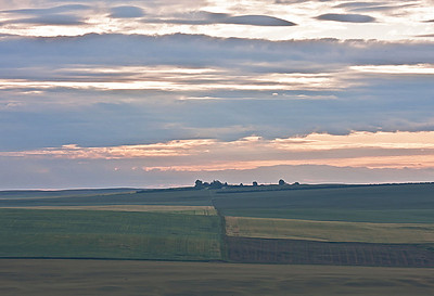 Buildings on the horizon separate the lines of the sky and the patterns of the land.