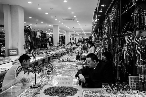 A male shopper examines merchandise at a local bead and jewelry store in Lhasa, TAR on July 24, 2018.
