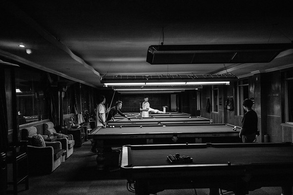 A group of young Tibetan tour guides play pool at a local pool hall in Lhasa,TAR on July 23, 2018.