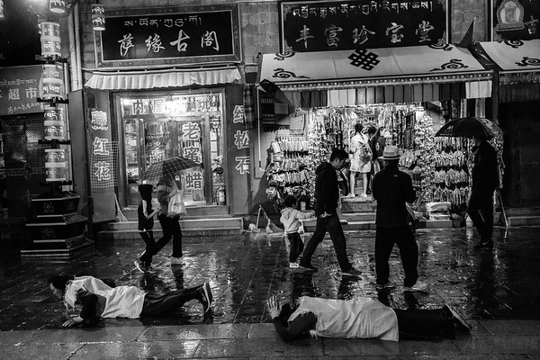 A pair of Tibetans prostrate in the rain around Barkhour Square in downtown Lhasa, TAR on July 23, 2018.