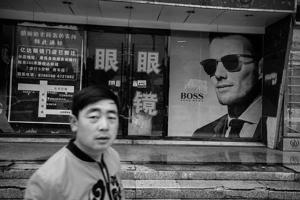A Chinese man walks by a Chinese store with a BOSS advertisement in downtown Lhasa on July 22, 2018.