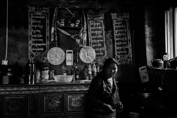 Tibetan woman preps a meal in her kitchen on July 23, 2018. The village she lives in is located in Dagze.