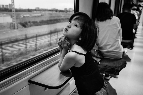 A young girl rest her elbows on a small table underneath a window in the hallway of the hard sleeper car on the Qinghai-Tibet Railway train in July 2018.