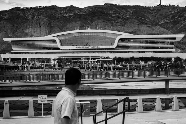 A man walks adjacent to the Xining Railway Station in the People's Republic of China in July 2018. This is where the world famous Qinghai-Tibet Railway begins.