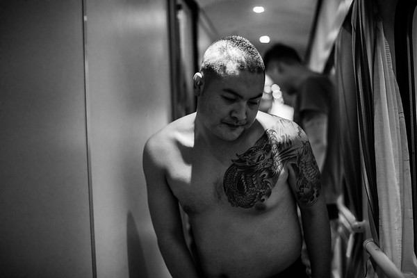 A shirtless Chinese man walks down the hallway of the first class car on the Qinghai-Tibet Railway train in July 2018.