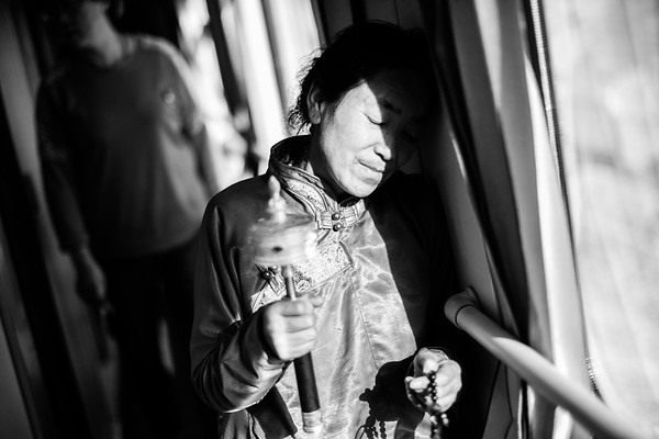 A Tibetan woman spins her prayer wheel and holds her mala beads, which are considered to be spiritual tools, in the hallway of a hard sleeper car in July 2018.