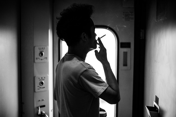 A male passenger smokes a cigarette in the first class car of the Qinghai-Tibet Railway train in 2018.