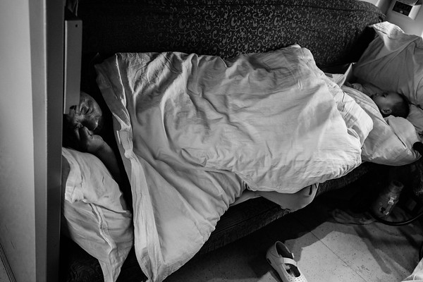 A man and child sleep in their first class car on the Qinghai-Tibet Railway train in July 2018.