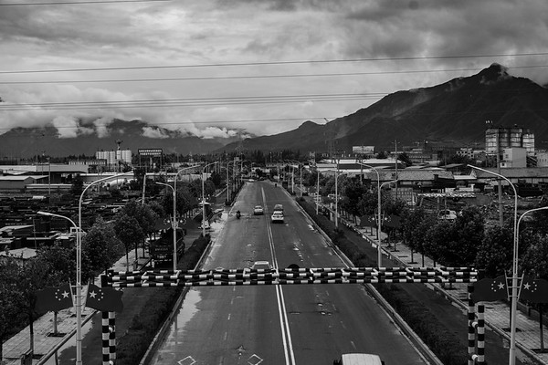 The outskirts of Lhasa, the capital city of Tibet Autonomous Region, is developed with roadways and decorated with Chinese flags in July 2018.