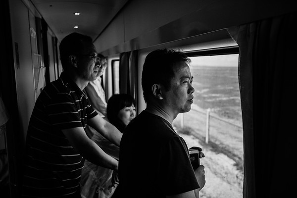 First class passengers gaze at the landscape out of the window on the Qinghai-Tibet Railway train in July 2018.
