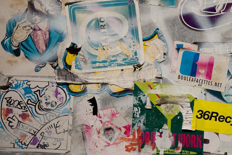 108 - Stickers<br /> -----------------<br /> Photo prise sur l'arrière d'un panneau. En y regardant de plus près il y a une foule de choses collées ou dessinées sur les murs de Paris.
