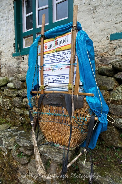 A porter's basket with some essential supplies in the form of San Miguel beer  between Lukla and Phakding