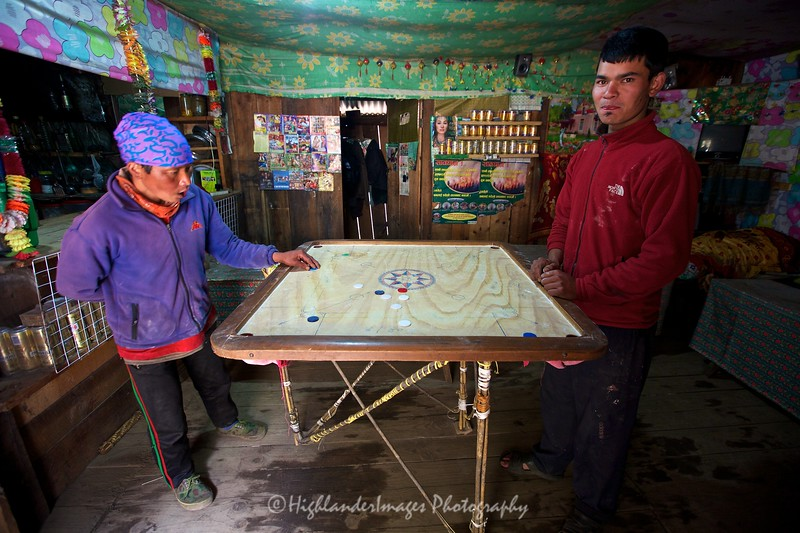 """This board game known as Carrom is very popular in Nepal and was seen being played in numerous small villages, like here between Phakding and Monjo.<br /> <br /> Carrom (also known as Karrom) is a """"strike and pocket"""" table game of Eastern origin similar to billiards and table shuffleboard. It is found throughout the East under different names though most non-eastern people know it by the East Asian name of Carroms (or Karrom). It is very popular in India, Pakistan, Bangladesh, Sri Lanka and surrounding areas. In the Indian sub-continent, many clubs and cafes have regular tournaments. Carrom is very commonly played within families and other functions. Different standards and rules exist in different areas."""
