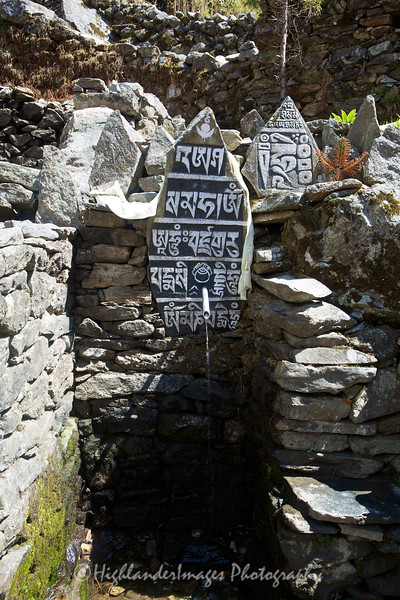 An inscribed Mani stone and fountain between Monjo and Lukla.