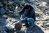 A stone worker chips away at a large rock as they mend a bridge between Phakding and Lukla.