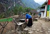A woman washes her clothes outside her house between Phakding and Monjo.