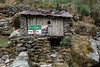 A small wooden hut with an advert for a barber shop in Lukla and an aptly named bar called Altitude Pub