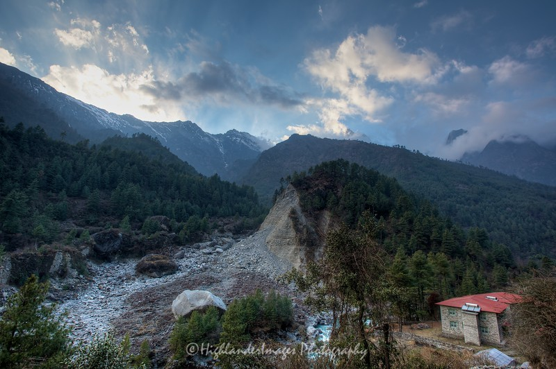 Close to Phakding the trail came closer to the Dudh Kosi river.Here you can see some gigantic boulders and signs of significant erosion. A stunning sky and mountains act as a wonderful backdrop to this scene.