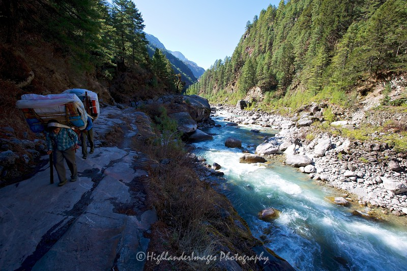 Sherpa porters slowly making their way up the trail between Jorsalle and Namche Bazaar and alongside the beautiful Dudh Kosi River.