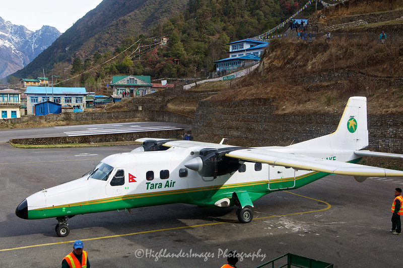 """Lukla Airport, now known as Tenzing-Hillary Airport, is rated as one of the most dangerous airports in the world and a program titled """"Most Extreme Airports"""" broadcast in the History Channel in 2010, rated the airport as the most dangerous airport in the world.<br /> <br /> So this was to be our arrival point for this start of our 7 day Himalayan trek up the Everest Base Camp trail - as if the trek was not hard enough we had to survive the landing and then the take-off from this incredible runway.<br /> <br /> The airport is popular because Lukla is the place where most people start the climb to Mount Everest Base Camp. There are daily flights between Lukla and Kathmandu during daylight hours, in good weather. Although the flying distance is short, rain commonly occurs in Lukla while the sun is shining brightly in Kathmandu. High winds, cloud cover and changing visibility often mean flights can be delayed or the airport closed completely. The airport is contained within a chain link fence and patrolled by the Nepali armed police or civil police around the clock.<br /> <br /> The airport's paved asphalt runway is only accessible to helicopters and small, fixed-wing, short-takeoff-and-landing aircraft, such as the De Havilland Canada DHC-6 Twin Otter or Dornier Do 228. Tara Air also operates two Pilatus PC-6 Turbo Porter aircraft that visit Lukla on a charter basis. The runway is 460 by 20 m (1,510 by 66 ft) with a 12% gradient. The elevation of the airport is 2,800 m (9,200 ft).<br /> Aircraft can only use runway 06 for landings and runway 24 for takeoffs. Due to the terrain, there is no prospect of a successful go-around on short final. There is high terrain immediately after the northern end of the runway and a steeply angled drop, of about 2,000 m (6,600 ft) at the southern end of the runway, into the valley below.<br /> The apron has four stands and there is one helipad located 140 m (460 ft) from the control tower. No landing aids are available and the only air """