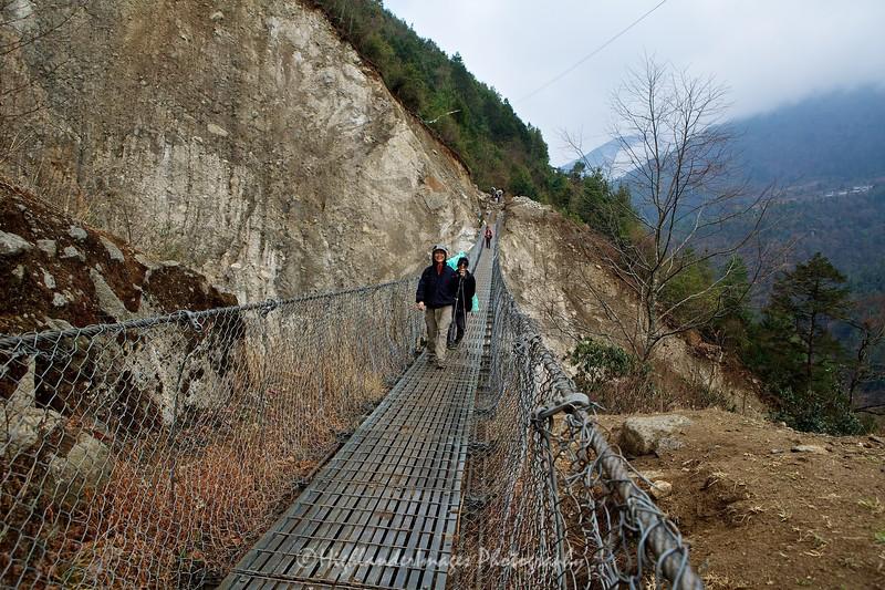 Suit Yoo nervously crosses her first suspension bridge between Lukla and Phakding