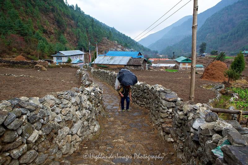 A porter with umbrella between Koshigaun village and Phakding