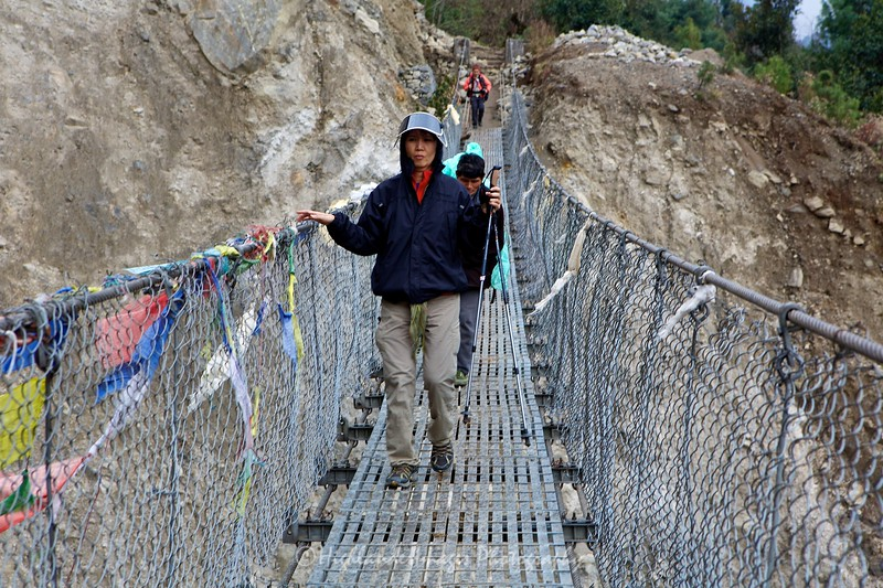 Suit Yoo nervously crosses her first suspension bridge between Lukla and Phakding