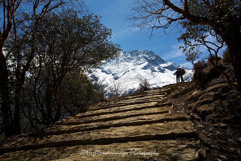 Two trekkers silhouetted against the bright snowy mountains on the trail between Namche Bazaar and Tengboche.