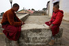 Two monks outside the Tengboche monastery play a makeshift board game with stones.