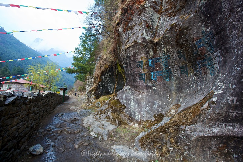 Arriving at Phakding from Lukla with more script writing on the rocks and streams of colourful prayer flags