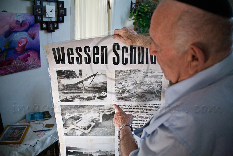 Yosef Kleinman, 82, Auschwitz-Birkenau, Dachau-Kaufering, survivor, displays an American poster posted around Kaufering to inform the local residents of the atrocities happening inside the camps. Jerusalem, Israel. 17-Apr-2012.