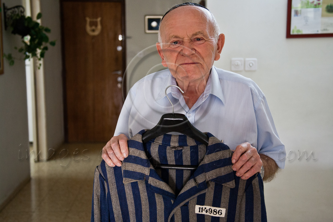 Yosef Kleinman, 82, Auschwitz-Birkenau, Dachau-Kaufering, survivor, displays his prisoner uniform from the Dachau-Kaufering camp. He takes pride in documentation of the Holocaust through saved relics from the past. Jerusalem, Israel. 17-Apr-2012.