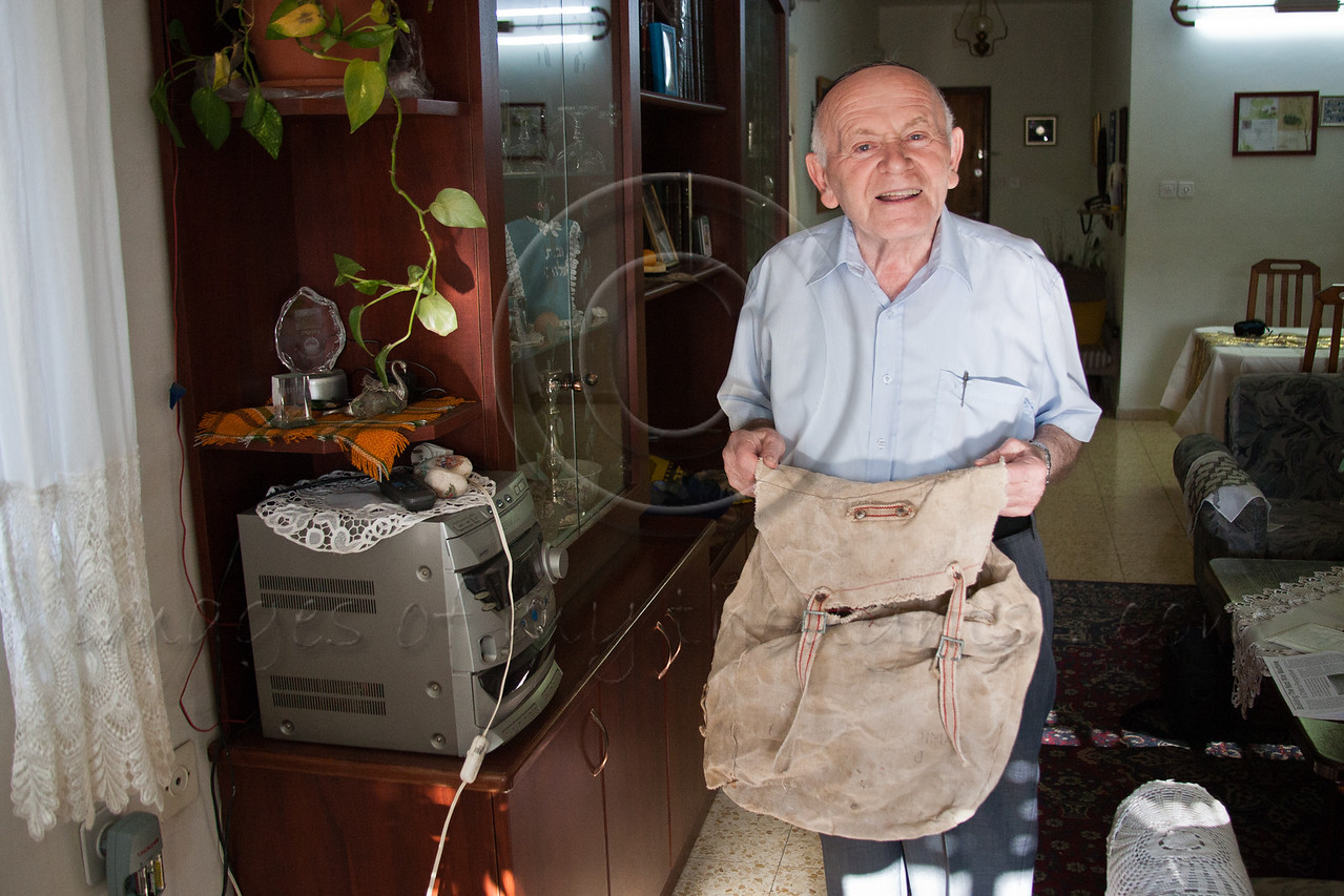 """Yosef Kleinman, 82, Holocaust survivor, displays a worn rucksack in which he packed all his worldly belongings as he boarded the """"Four Freedoms"""" illegal immigration boat from Bocca di Magra, Italy, to Palestine in August 1946. Jerusalem, Israel. 17-Apr-2012."""