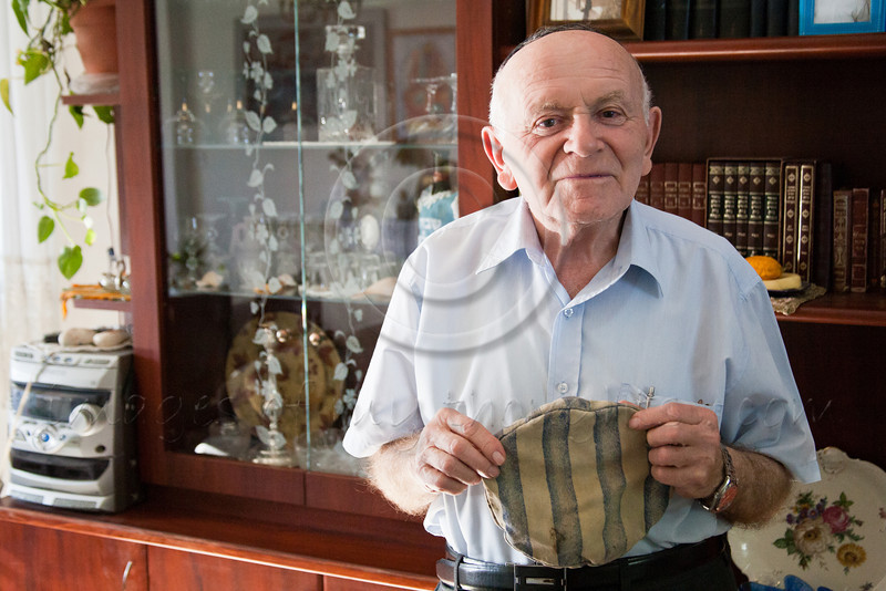 Yosef Kleinman, 82, Auschwitz-Birkenau, Dachau-Kaufering, survivor, displays his prisoner hat from Auschwitz-Birkenau Camp. He takes pride in documentation of the Holocaust through saved relics from the past. Jerusalem, Israel. 17-Apr-2012.