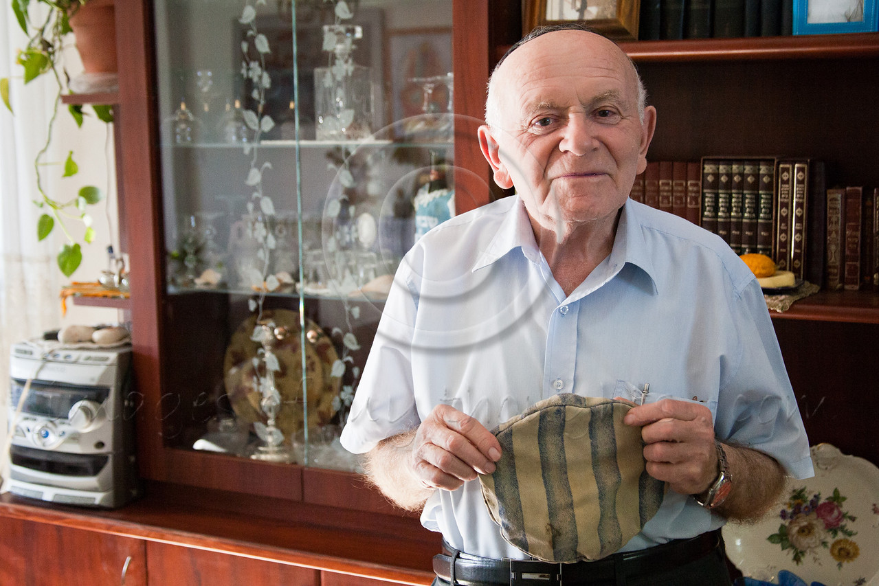 Yosef Kleinman, 82, Auschwitz-Birkenau, Dachau-Kaufering, survivor, displays his prisoner hat from Auschwitz-Birkenau Camp. He takes pride in documentation of the Holocaust through saved relics from the past. Jerusalem, Israel. 17-Apr-2012.