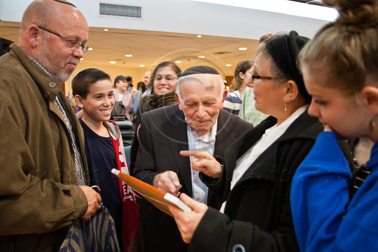 Yosef Kleinman, 82, Holocaust survivor, is surrounded by excited members of the Bereshit (Genesis) Synagogue following his address on the eve of Holocaust Martyrs' and Heroes' Remembrance Day. Bet-Shemesh, Israel. 18-Apr-2012.