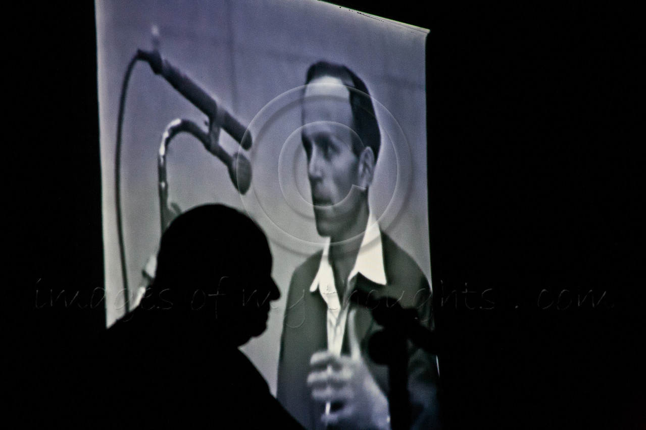 Silhouette of Yosef Kleinman, 82, Holocaust survivor, as a movie clip is projected of his 1961 testimony in the trial of Adolph Eichmann, at the Bereshit Synagogue on the eve of Holocaust Martyrs' and Heroes' Remembrance Day. Bet-Shemesh, Israel. 18-Apr-2012.