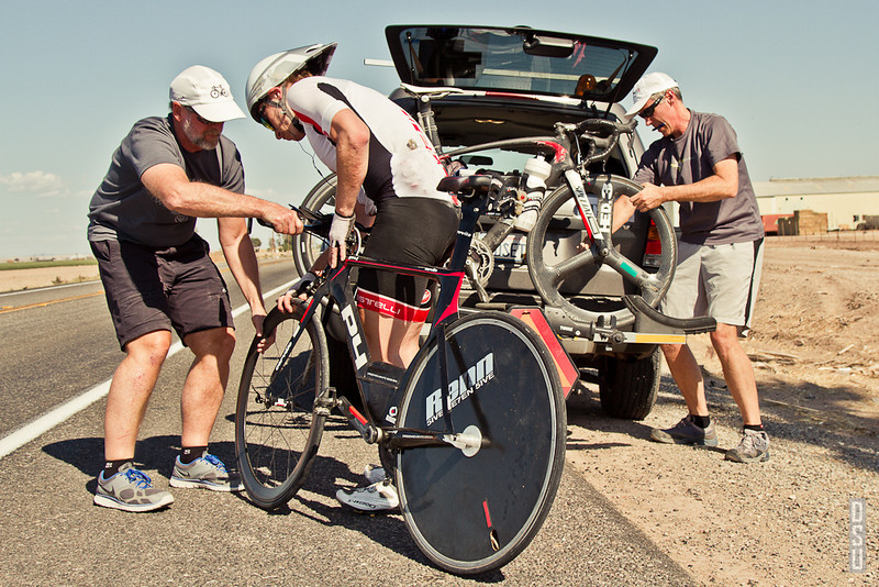 There is a support vehicle that follows Adam throughout the course. If Adam needs to make any changes to his gear, or if he has a mechanical problem with one of his bikes, the crew can fix the problems quickly without losing too much time. Here, the team swapped a front wheel that developed a flat tire.