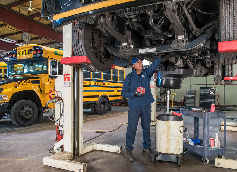 Boston Public Schools' mechanic performs routine maintenance on one of the district's propane buses.
