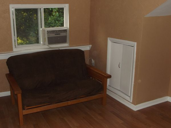 The studio-efficiency on the 3rd floor features a sitting area furnished with a futon. The sitting area has a vaulted ceiling with fan and light above it. Some storage is possible under the eaves behind the white doors.