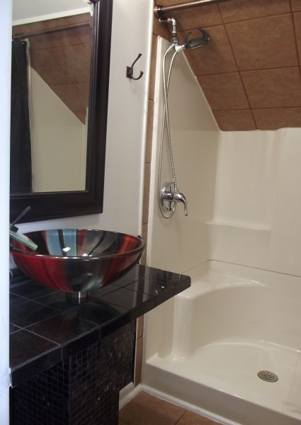 The bath in the third floor studio contains a two-person shower with flex-hose attachment, and a vessel sink on a pedestal with waterfall faucet. The mirror has a lighting fixture hanging over it, while the room also contains an exhaust fan, overhead light and infra-red heat lamp.