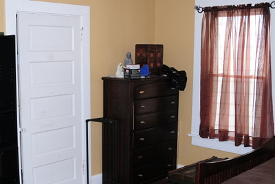 The larger of the two bedrooms on the second floor features a closet and windows on two walls. (Furniture not included with this unit.)