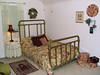 Bedroom in rear of house. Mattress is double width - smaller than queen size. Futon mattress sits on bed board. Brass frame has been replaced.