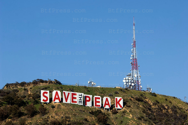 "Protesters are covering the world-famous Hollywood sign with panels reading ""Save the Peak."" The group has raised about $7 million of the roughly $12 million needed to buy the Cahuenga Peak property from the Chicago area-based owners. The owners had announced plans to develop the 138-acre parcel into luxury homes."